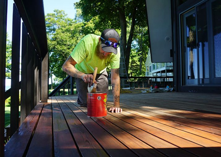 Vork Brothers team member painting an outdoor deck of residential home